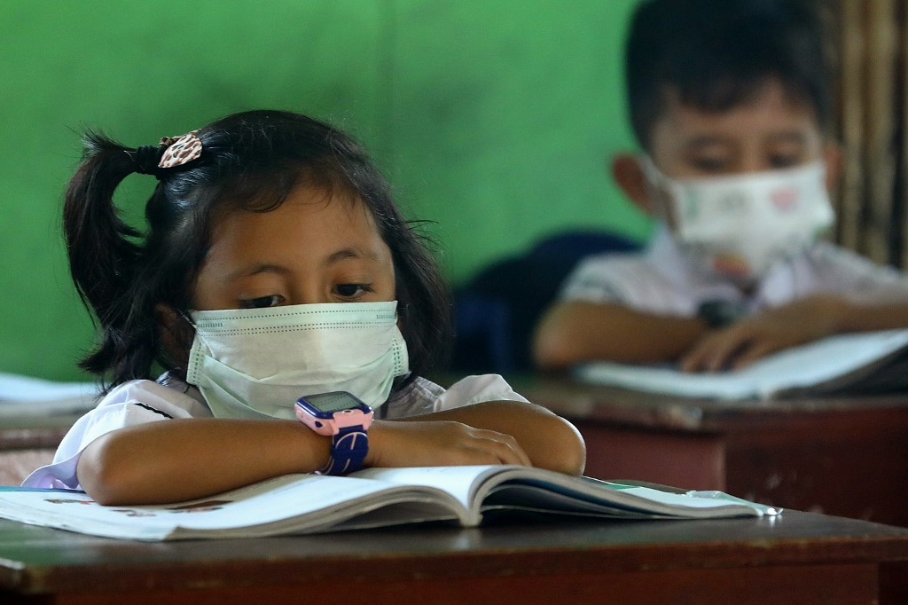 Elementary school children wearing face masks sit in a classroom on Natuna island in Riau islands province on February 4, 2020. - Hundreds of residents of Indonesia's Natuna island protested February 3 at the government's decision to use it to quarantine evacuees from the Chinese city at the epicentre of the coronavirus outbreak. (Photo by RICKY PRAKOSO / AFP)